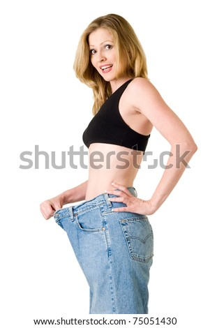 Attractive slim blond woman demonstrating weight loss by wearing an old pair of jeans and holding out to show how big the pants are