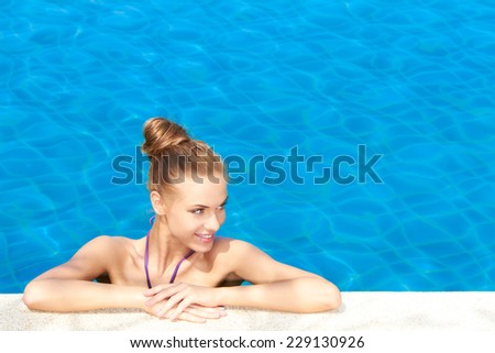 Attractive Slim Woman with Closed Hair at the Edge of Beautiful Pool Smiling at her Left Side.