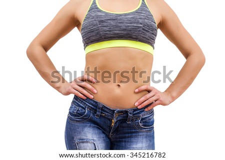 Attractive Slim Woman with perfect healthy fit body, showing her thin waist.  Caucasian young female in jeans, over white background. Unrecognizable person.Diet and weight loss concept. - stock photo