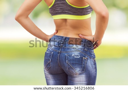 Attractive Slim Woman with perfect healthy fit body, showing her thin waist.  Caucasian young female in jeans, over nature background. Unrecognizable person.Diet and weight loss concept. - stock photo