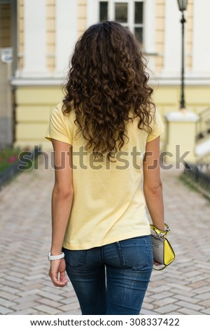 Attractive slim young woman with curly brown hair is walking on the old European city. She is wearing a yellow T-shirt and blue jeans, ladies handbag in her hand. - stock photo