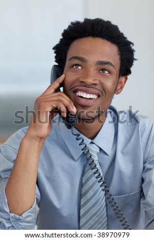 Attractive smiling Afro-American young businessman on phone in office - stock photo
