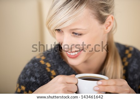 Attractive smiling blond woman enjoying her cup of coffee in a coffee shop