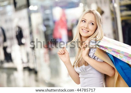 Attractive smiling blonde on shopping in shop - stock photo