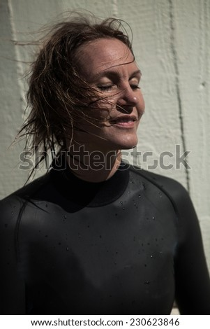 Attractive smiling brunette female swimmer wearing black wetsuit with wet hair and eyes closed and sunlight in face - stock photo