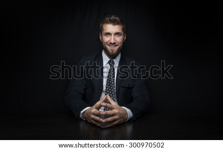 Attractive, smiling business man in front of a black background  - stock photo