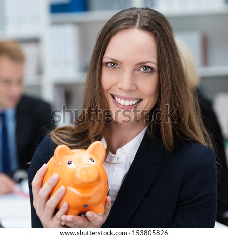 Attractive smiling business woman holding a piggy bank - stock photo