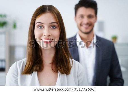 attractive smiling businesswoman standing inside the workplace with colleague in background - stock photo
