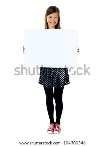 Attractive smiling cute girl holding blank poster against white background