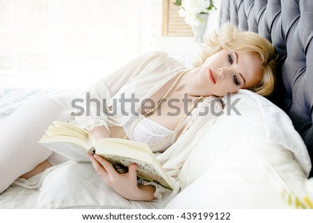 Attractive smiling excited woman reading a book in the morning.
