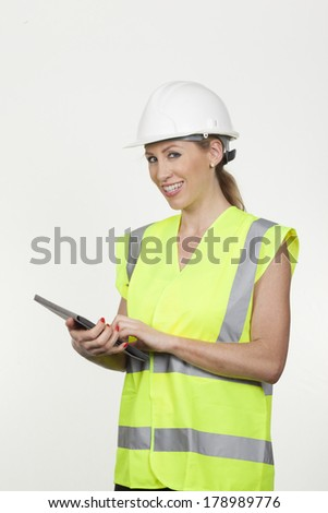 Attractive smiling female architect, structural engineer or safety officer wearing a hardhat and high visibility fluorescent jacket holding a tablet computer in her hands isolated on white - stock photo