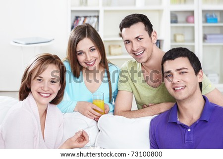 Attractive smiling friends at home - stock photo