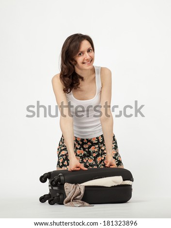 Attractive smiling girl packing her suitcase