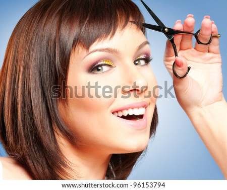 Attractive smiling girl with scissors, cutting her hair - stock photo
