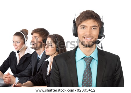 Attractive Smiling handsome positive young businessman and colleagues in a call center office, support phone operators with headset at workplace over white background, agent friendly looking at camera - stock photo