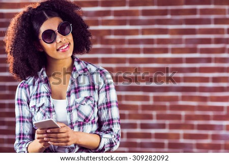 Attractive smiling hipster holding smartphone against red brick background - stock photo