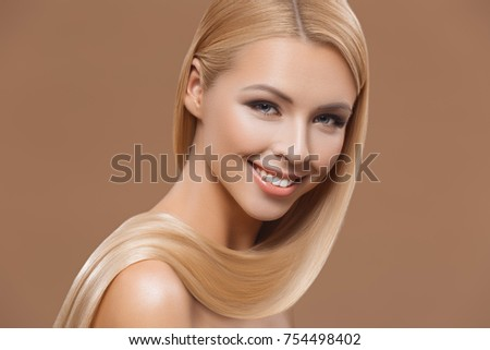 attractive smiling model with long blond hair, isolated on brown, haircare concept