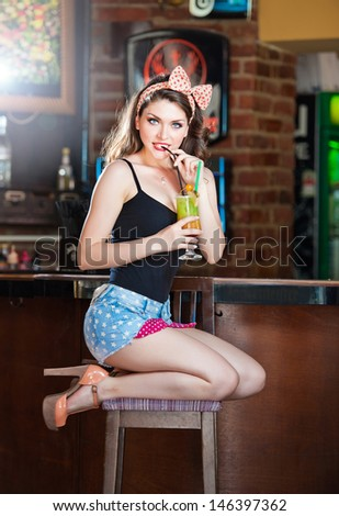 Attractive smiling pinup woman in denim shorts sitting on bar stool and drinking lemonade. Gorgeous Pinup model with white bow on her head and black bra drinking and posing in vintage bar - stock photo