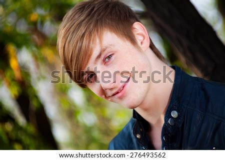 attractive, smiling, red-haired guy on nature. close-up portrait