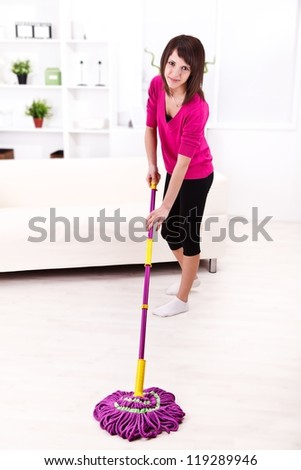 Attractive smiling woman cleaning the floor with a mop - stock photo