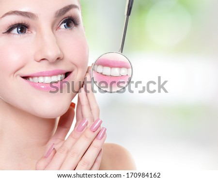attractive smiling woman face with health teeth close up and a dentist mouth mirror, dental care concept - stock photo