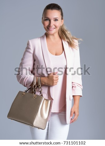 Attractive smiling woman holds the golden handbag over white background