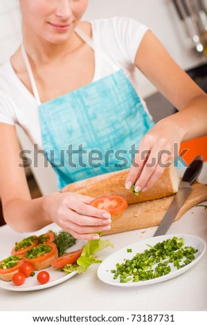 Attractive smiling woman preparing fresh healthy sandwiches in her kitchen - stock photo