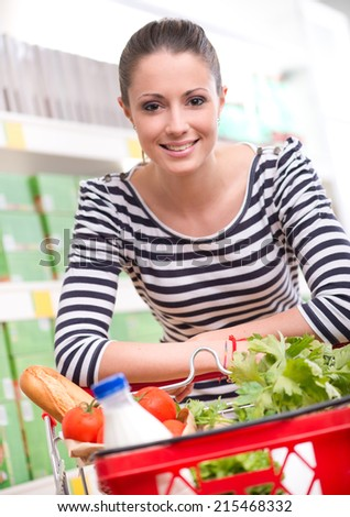 Attractive smiling woman shopping at store leaning to shopping cart. - stock photo