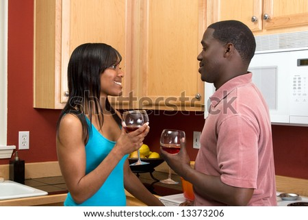 Attractive smiling young African American couple looking at each other standing in a kitchen holding wine glasses.  Horizontally framed shot with the woman's face towards the camera.