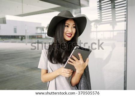 Attractive smiling young Asian woman searches for information on the Internet on her tablet outside the office - stock photo