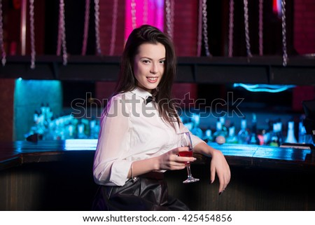 Attractive smiling young brunette woman wearing white shirt and black bow tie sitting at bar counter, holding glass of pink cocktail - stock photo