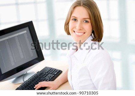 Attractive smiling young business woman using computer at work desk - stock photo