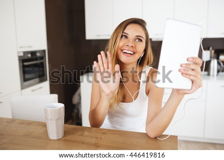 Attractive smiling young girl sitting at dinner table holding tablet and talking with friends via messenger