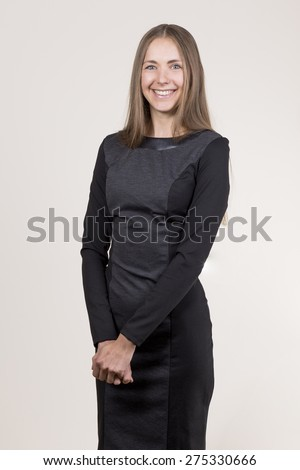 Attractive smiling young woman in a black dress crossing her hands looking at camera - stock photo