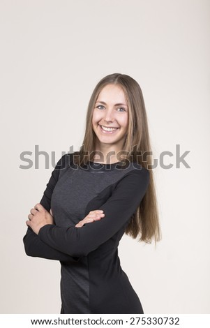 Attractive smiling young woman in a black dress looking at camera. hands crossed - stock photo