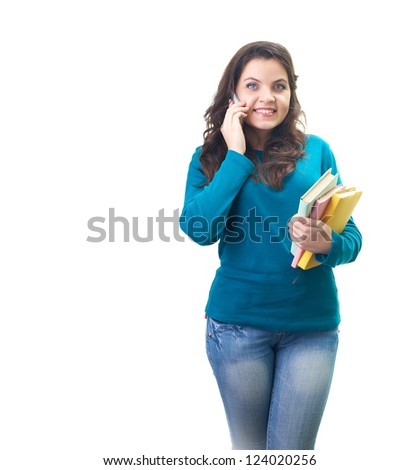 Attractive smiling young woman in a blue shirt talking on a mobile phone and holding a colorful book. Isolated on white background