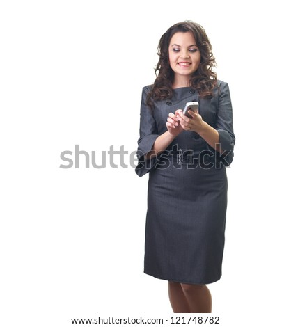 Attractive smiling young woman in a gray business dress holding a mobile phone and looks at him. Isolated on white background