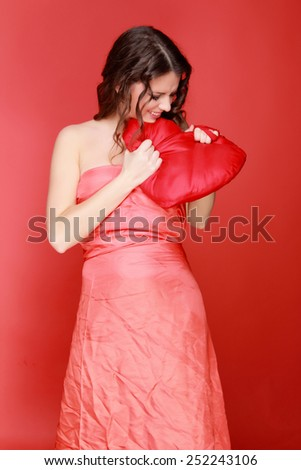 Attractive smiling young woman in beautiful red dress holding a big red heart symbol of love and Valentine's Day on a red background - stock photo