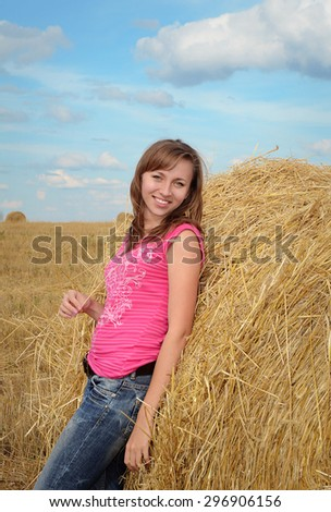 Attractive smiling young woman in casual wear near the haystack - stock photo