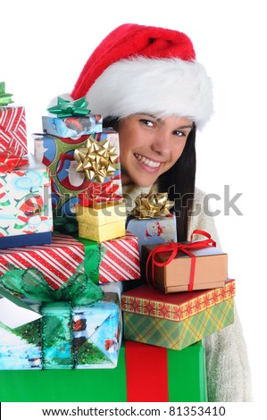 Attractive smiling young woman peeking around a large stack of Christmas presents. Closeup in vertical format over white.