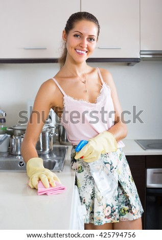 Attractive smiling young woman washing kitchen top with detergent