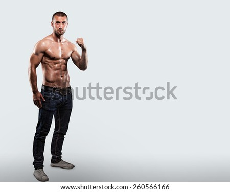 Attractive sports man in jeans and shirtless - stock photo