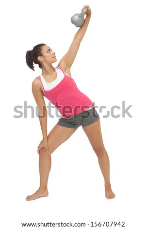 Attractive sporty brunette holding grey kettle bell on white background