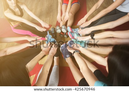 Attractive sporty girls are doing exercise together - stock photo