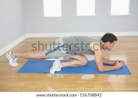 Attractive sporty man exercising on blue mat in bright room