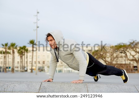 Attractive sporty man working out at early morning outdoors, male runner doing push ups exercise outside - stock photo