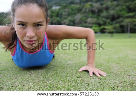 attractive, sporty woman doing push-ups outdoors in the park - stock photo