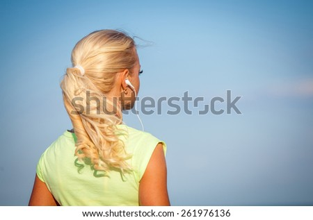 Attractive sporty young woman standing on the beach taking a break from exercising and listening to music with her mp4 player and head phones against a blue sky - stock photo