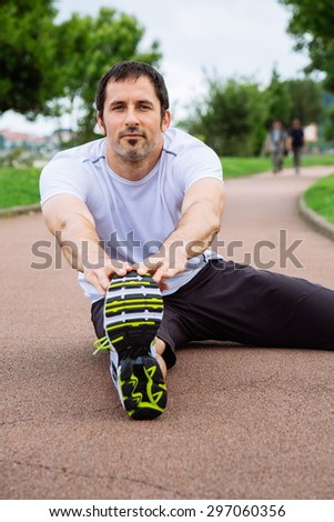 Attractive spotrsman doing stretching exercises outdoors in a track - stock photo