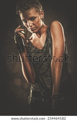 Attractive steampunk singer with microphone  - stock photo